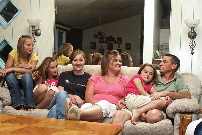 The Swindler family is shown at their home on Moffat County Road 35 south of Craig. From left, Jazmine, 13, Brittany, 11, Kylee, 15, Janese, Stephenie, 8, and Steve squeeze together on the couch. Steve supports his family through his job at Colowyo Coal Co., as an equipment operator.