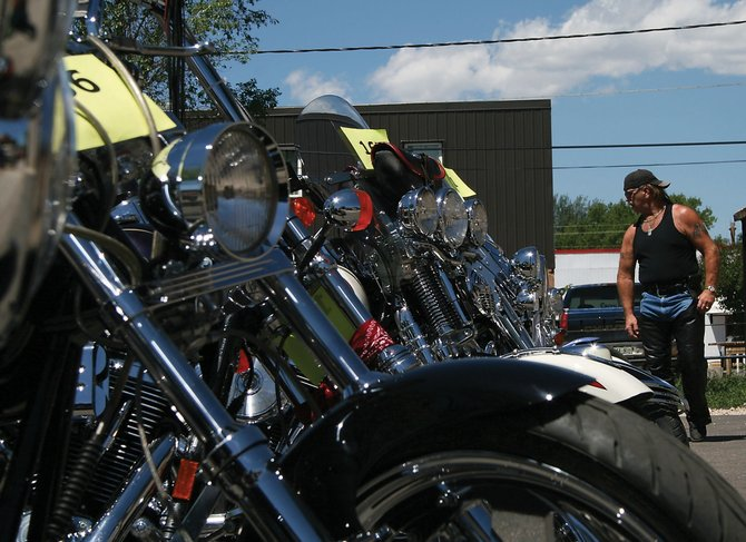 Bill Smith, of Ashville, N.C., admires a line of motorcycles at the Bear River Young Life & Colorado Cruisers Car & Motorcycle Show on Saturday in downtown Craig. Smith won an award for farthest distance traveled from home.