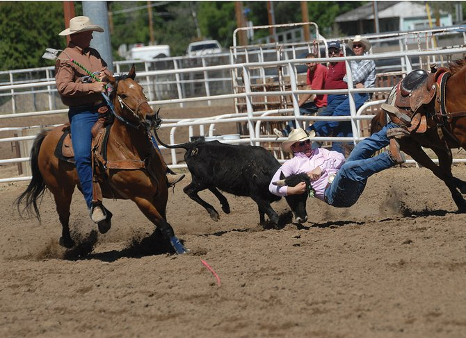 Garrett Carroll, right, tries to wrestle his steer to the ground Saturday during the Colorado State High School Rodeo finals in Moffat County. Carroll said there is no thrill bigger in rodeo for him than jumping off his horse and taking down a steer.