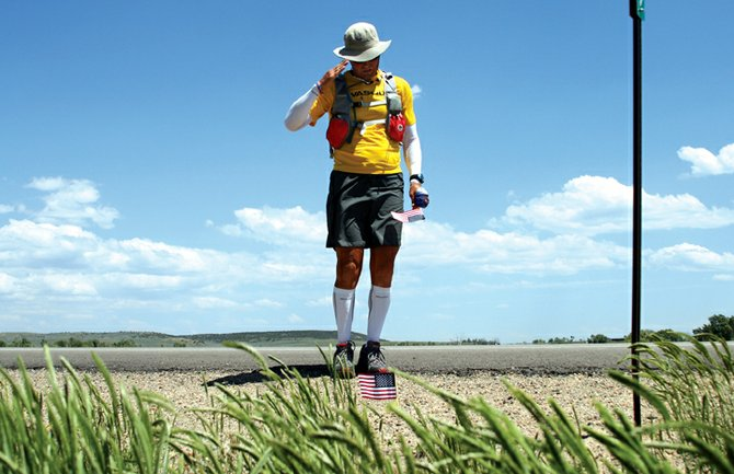 Mike Ehredt, of northern Idaho, salutes an American flag Tuesday at mile marker 49 on Wyoming Highway 789, north of Baggs, Wyo. Ehredt is making a cross-country trek on foot, placing a flag at each mile marker in honor of the 4,400 servicemen and women who have died in Iraq.  A meet-and-greet in Ehredt's honor is scheduled for 7 p.m. tonight at the Veterans of Foreign Wars Post 4265, 419 E. Victory Way.
