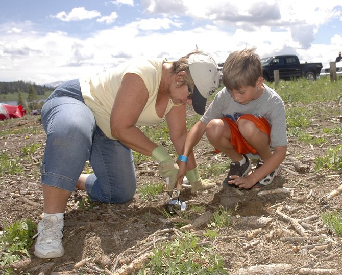 Patti Rackstein and her grandson Colton Mays plant a lodgepole pine seedling Saturday at Steamboat Lake State Park. The Racksteins live in Florida and have a house in Steamboat Springs, and Rackstein and her husband, Andy, brought twins Colton and Harper out to help with ReTree Colorado. The Mayses also live in Florida.