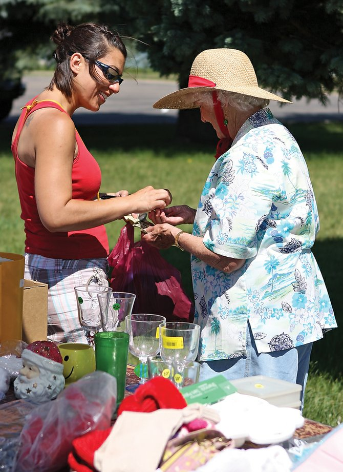 "Stephanie Beckett, left, pays Nina Lawton for items she found Saturday at the ""Junk in the Trunk"" yard sale in the parking lot at First Congregational United Church of Christ. Proceeds benefited the church's capital campaign, which will help pay off a new heating system."
