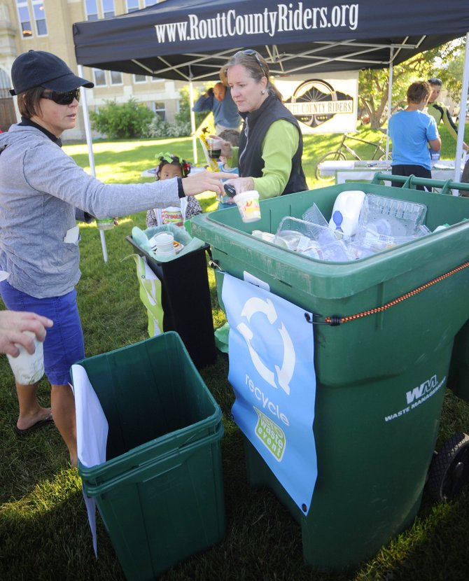Yampa Valley Sustainability Council Chairwoman Angela Ashby, right, shows Kristin Hager where to put her recyclables Wednesday in front of the Routt County Courthouse during the Bike to Work Week breakfast.