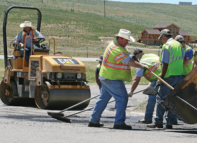 The City of Craig road and bridge department crew lays asphalt to patch a section of road Monday near the intersection of Crescent Drive and Riford Road. Crews are patching areas around the city in preparation for larger chip-sealing projects, which will start in mid-July.