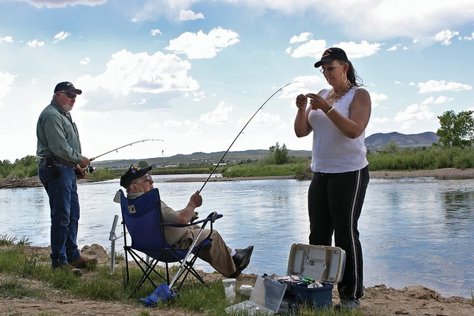 Joe Rodriguez, middle, has a line baited by Martha Henley, right, while her husband, Larry Henley, left, holds his rod Tuesday along the Yampa River near Loudy-Simpson Park. Craig was named No. 68 on Outdoor Life magazine's list of the top 200 towns for sportsmen to live.