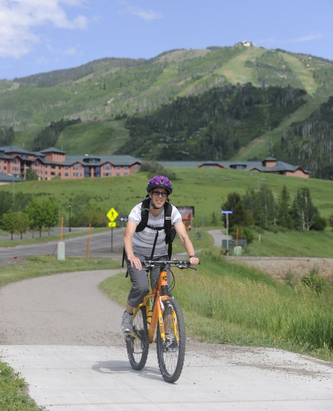 Steamboat Springs resident Diane Carter commutes between jobs on her bike Wednesday alongside Mount Werner Road. Cycling momentum in Steamboat is building as local activists hope to make a more bike-friendly community, one that is worthy of the name Bike Town USA.