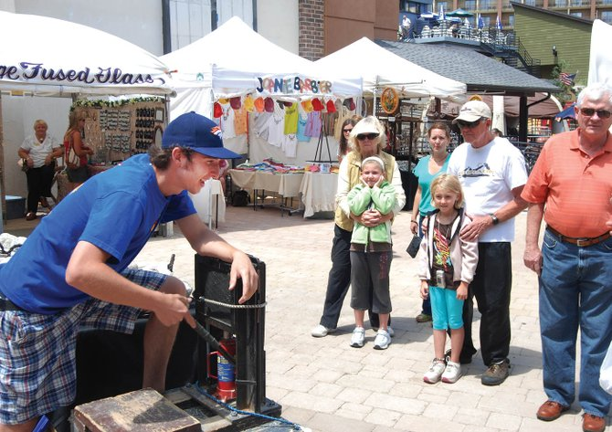 Dusty Atkinson, left, uses an 8-ton jack to split rock geodes and reveal their crystalline beauty for customers from Kentucky in Gondola Square on Friday. Atkinson and his father, Leo, of Steamboat, are the Geode Guys. They were taking part in the Art on the Mountain festival which continues from 10 a.m. to 4 p.m. today and Sunday.
