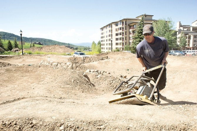 Clay Schrader compacts the soil on the new pump track that is being built in Ski Time Square. The track is nearing completion and could be open to the public next week.