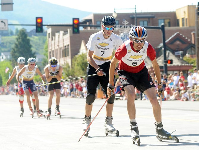 Johnny Spillane, right, and Erik Lynch lead a pack of roller-skiers Sunday during the Nordic combined event in downtown Steamboat Springs.