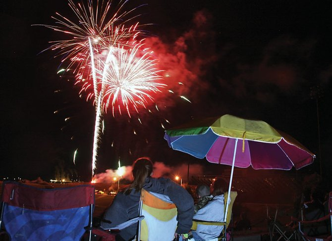 Spectators brought out camping chairs and umbrellas to watch the Fourth of July fireworks show Sunday at Moffat County High School. Some people arrived more than an hour before the show to make sure they had a front row seat.