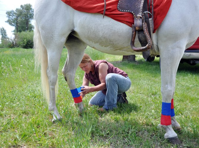 Yampa resident Jill Andrews applies holiday leg wraps to her horse Annie before the start of Yampa's Fourth of July Parade on Sunday. Andrews said she puts her horses in the parade every year.