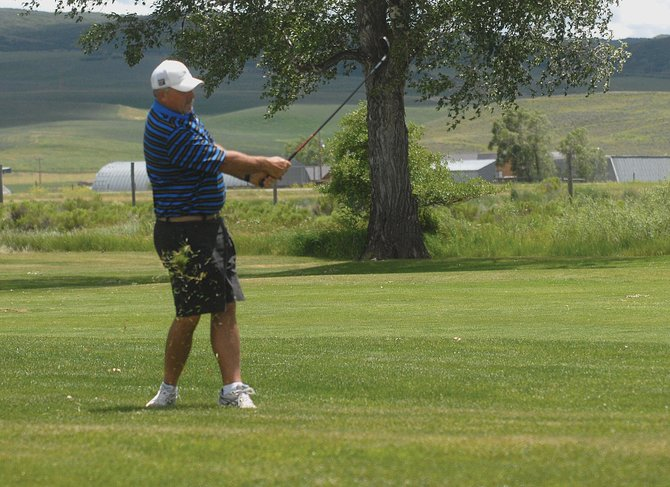 Tim Rolando, of Craig, hits his ball along with some grass at Yampa Valley Golf Course. More than $15,000 in prizes were awarded after the three-round tournament, which ended Sunday.