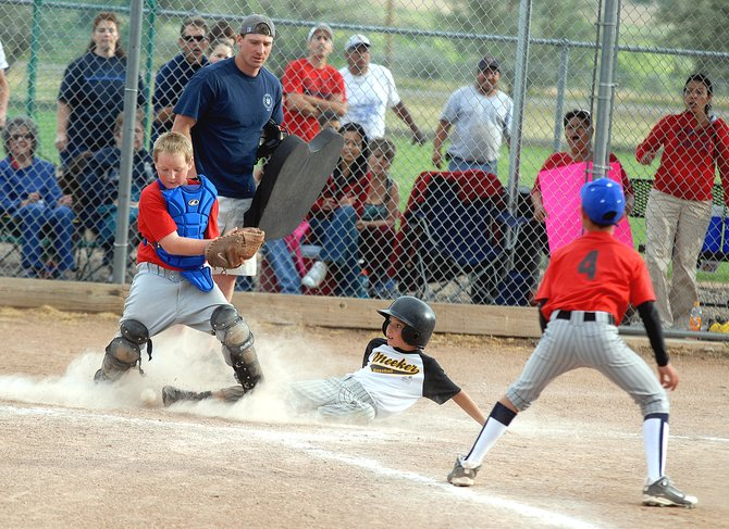 Meeker II runner Stephen Walsh, 9, slides into home plate during the Craig Parks and Recreation 8- to 10-year-old end-of-season championship game. Meeker II beat Cook Chevrolet 3-0 on Thursday night be crowned the champions.