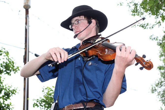 James Allen, 16, of Niwot, plays the violin during Thursday Farmer's Market at Alice Pleasant Park. James played as part of a duet with his grandfather, John Allen, on guitar during the event.