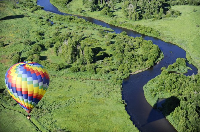 A balloon floats alongside the Yampa River on Friday morning during the media day balloon launch. The Hot Air Balloon Rodeo begins at 6 a.m. Saturday at Bald Eagle Lake.