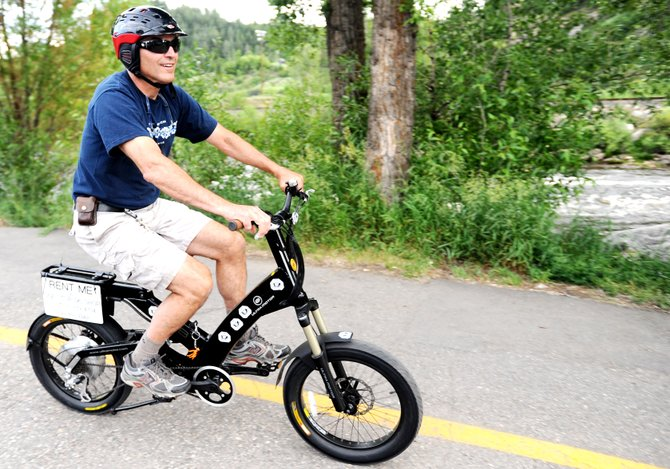 John Kole rides an electric bike at his downtown Steamboat Springs store, One Stop Ski Shop, in 2010. The bikes are growing in popularity.
