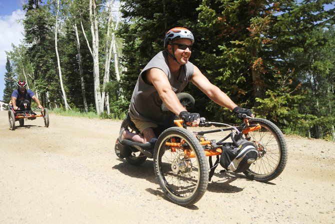 Bikin' the 'Boat Adaptive Cycling Camp organizer Craig Kennedy, right, rides Wednesday on a Mount Werner trail with Adaptive Adventures co-founder Matt Feeney. The camp offered people with disabilities and their families a chance to ride hand cycles, three-wheeled vehicles powered by the arms.
