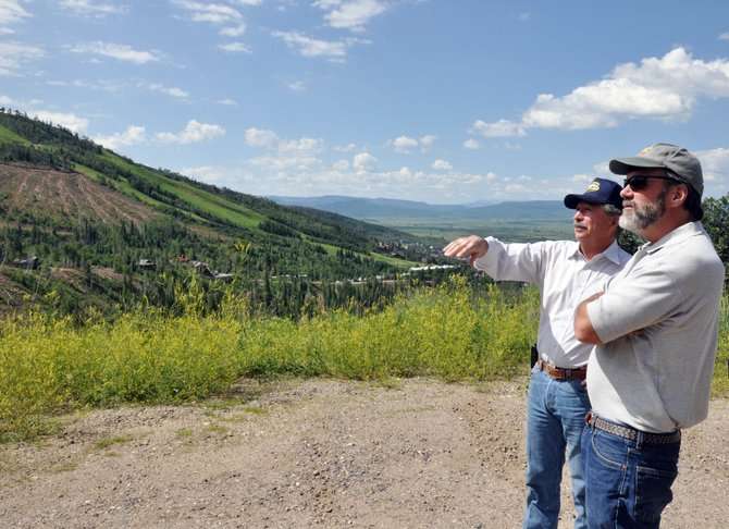 U.S. Rep. John Salazar, left, points toward the Burgess Creek logging site as he discusses efforts to remove beetle-killed pine trees in Steamboat Springs with district forester John Twitchell on Monday. Salazar was impressed by the scope and pace of the logging operations.