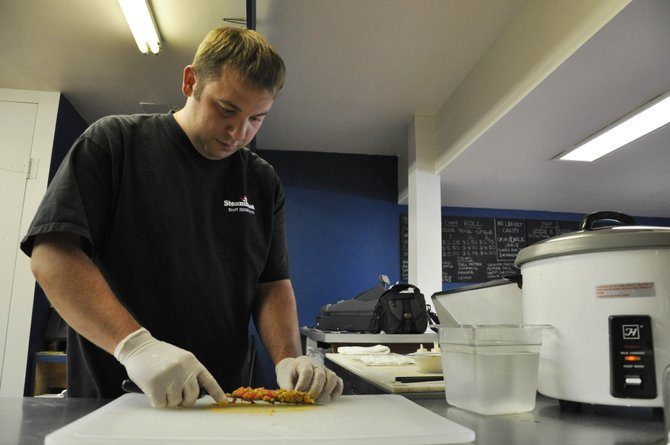 Spostas Sushi employee Luke Gordon prepares a spicy tuna roll Tuesday. Spostas lets customers customize their rolls by choosing from a variety of meats, sauces and vegetables.