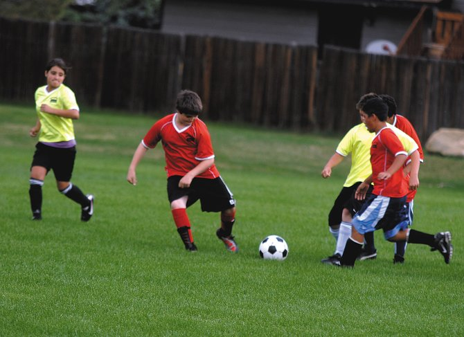Hugo Hernandez, 12, right, pushes the ball through the defense with the help of his teammates Tuesday evening. Craig Parks and Recreation youth soccer plays at 5:30 p.m. every Tuesday and Thursday at Woodbury Sports Complex.