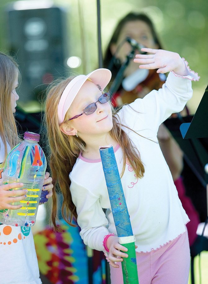 Zoe Welch, a member of the Boys & Girls Club of Steamboat, waves to the crowd while playing an instrument made out of recycled materials during the Music on the Green's performance of Music and Mother Nature at the Yampa River Botanic Park. The young musicians joined the Meridian Quartet for the performance.