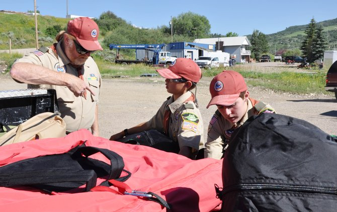 Scoutmaster Brian Berry, left, supervises Scouts Ian Caragol, center, and Matthew Espinosa as they load camping materials into the back of a truck Friday. The Scouts are attending the 2010 National Scout Jamboree on July 26.