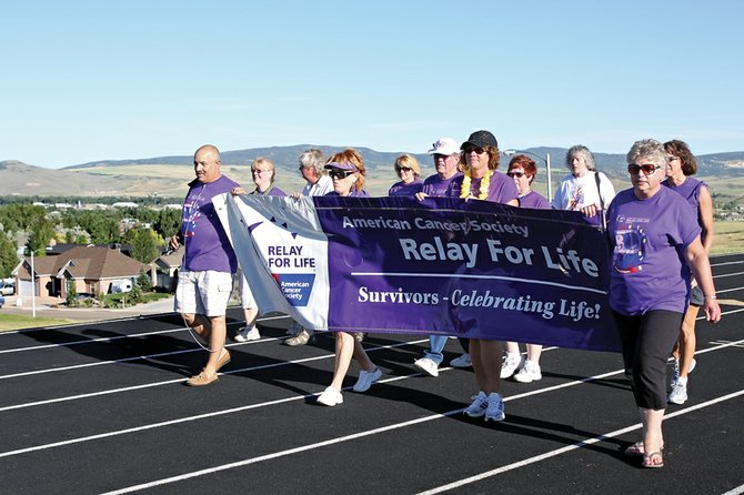 A group of cancer survivors walk the survivor lap Friday night during the fourth annual Craig Relay for Life at the Moffat County High School track. In the front row, from left, are Rick Faccenetti, Nancy Lee, Shannon Samuelson, and Cheri Race. About 160 walkers participated in the event with about 90 other people attending in support