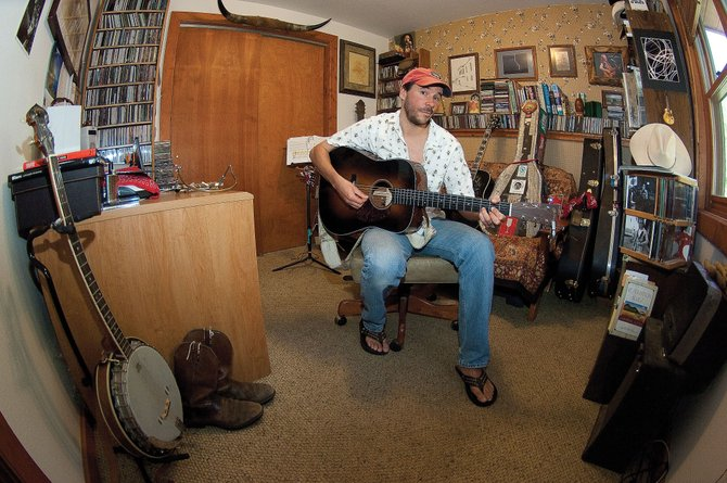Musician Trevor G. Potter plays his guitar in his home studio. Potter recently released his 2nd album.