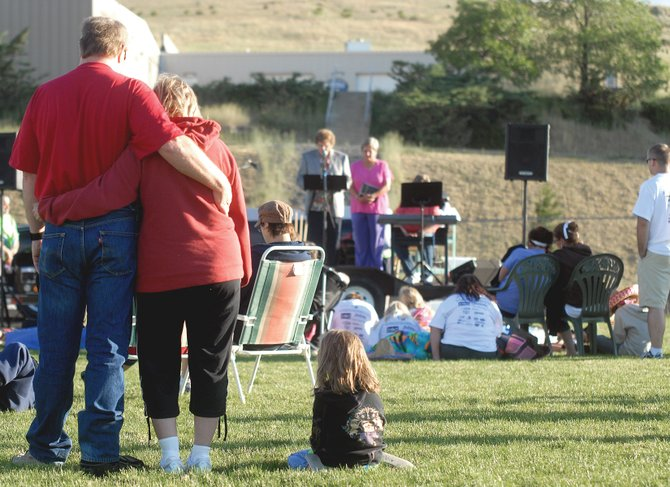 Dale Clark, left, stands with his arm around Melanie Hahn, as her daughter, Kaylee Hahn, 8, sits on the lawn during closing ceremonies Saturday morning at the Craig Relay for Life at the Moffat County High School track. Relay for Life, a fundraiser for the American Cancer Society, started at 6 p.m. Friday and continued until about 7 a.m. Saturday.