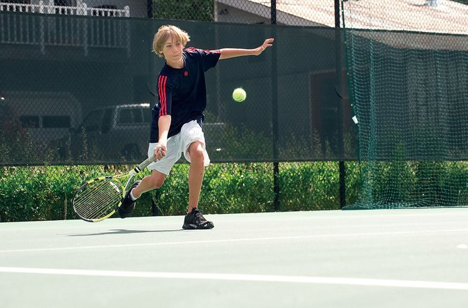 Nick Mathews, 14, returns a volley while playing on the tennis courts owned by the Old Town Hot Springs.