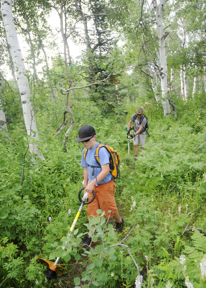 Sam Frackowiak, 10, and Dave Marrs work to clear a trail to be used during the Steamboat Springs Running Series Spring Creek Memorial 9-mile run Saturday.