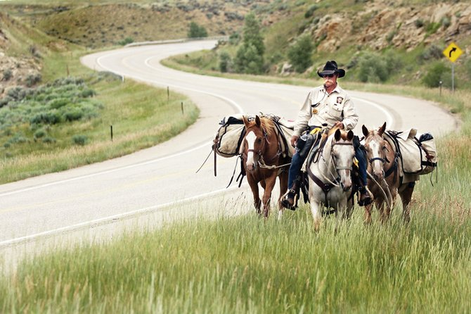 Idaho man Phil Dawson, of America Fundraisers Inc., rides south Thursday along Colorado Highway 13, near Craig. Dawson is embarking on a 7,500-mile trip to raise funds and awareness for organ transplants for children. He stopped Wednesday in Craig to rest his horses before moving on to Meeker.