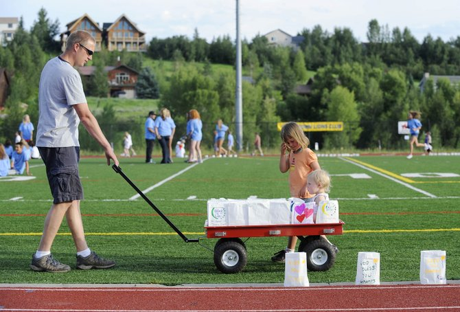 Stagecoach resident Todd Pedersen works with his daughters, Abi, 2, and Kaela, 5, to place luminarias around the Steamboat Springs High School track Friday during Relay For Life. The event this weekend raised $122,274 for cancer research.