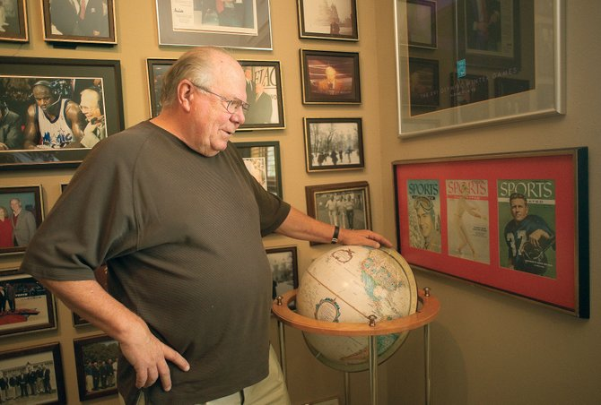 Sports broadcaster Verne Lundquist looks at a framed display of Sports Illustrated covers featuring Doak Walker, Skeeter Werner Walker and Buddy Werner that hangs on the wall of his office. It's one of the many items the longtime broadcaster has hanging on his wall marking special people or events in his life.