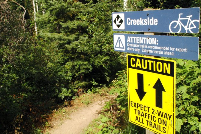 Signs at the top of Creekside Trail warn users of the dangers that may lie ahead on the trail that is popular with downhill-style mountain bikers. Although the official designation of the two-way traffic trail never was changed, for several years a sign at the bottom warned against hiking up it.