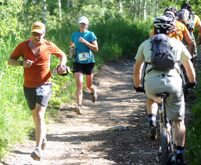 Avrom Feinberg, left, and Kris Anderson run past a trio of cyclists on Saturday during the Spring Creek Memorial run in Steamboat Springs. The run is intended to raise awareness for shared use of multi-use trails.