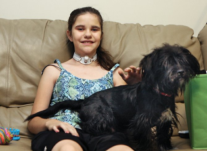 Katie Kennedy, 13, sits on a couch with one of her family's dogs, Scrappy, in the downstairs of her home Saturday in Craig. A benefit dinner for Kennedy, who was diagnosed with papillary thyroid cancer, will take place from 5 to 9 p.m. tonight at Vallarta's Mexican Restaurant in the Centennial Mall.