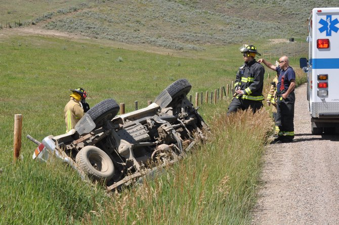 Steamboat Springs Fire Rescue responders check a Toyota pickup after a woman rolled the truck on Routt County Road 44 on Monday afternoon.