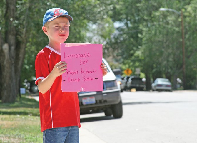 Tyler Burkett, 7, holds a sign Monday advertising a lemonade stand he is running with the help of his sister, Brianna, in the 700 block of Yampa Avenue. Tyler and Brianna said they are donating money raised from their stand to help cover the medical costs of Hannah Sixkiller, a former Craig girl who was recently diagnosed with cancer.