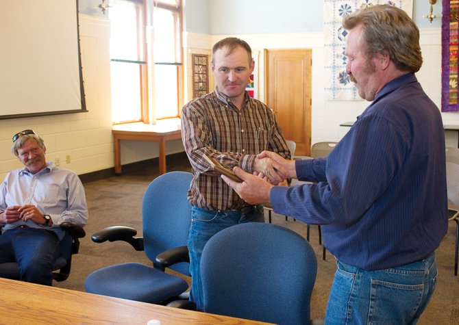 County Commissioner Doug Monger presents Routt County 4-H Agent Jay Whaley with a plaque during Monday afternoon's meeting honoring his service. Whaley will be leaving the Steamboat Springs office later this year to take a teaching position at Soroco High School in the fall.