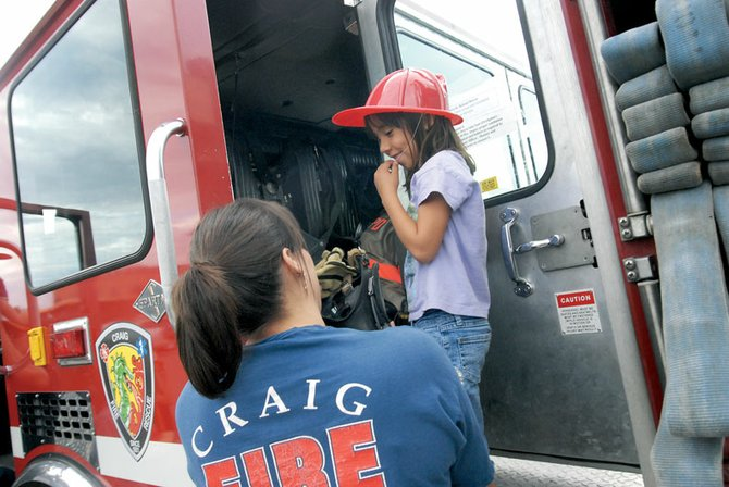 Firefighter Kamisha Siminoe shows Emily Gomez the inside of one of the Craig Fire/Rescue engines during the 2008 National Night Out. This year's event is scheduled for 4 p.m. Tuesday at Wendy's in Craig, and will include appearances by the fire department and various other agencies.