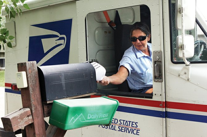 "Barb Sholes, 56, delivers mail to a residence Thursday on Essex Court. Sholes, a Craig resident, said a proposal to cut Saturday mail delivery is a ""bad idea"" and could affect businesses that depend on the service."