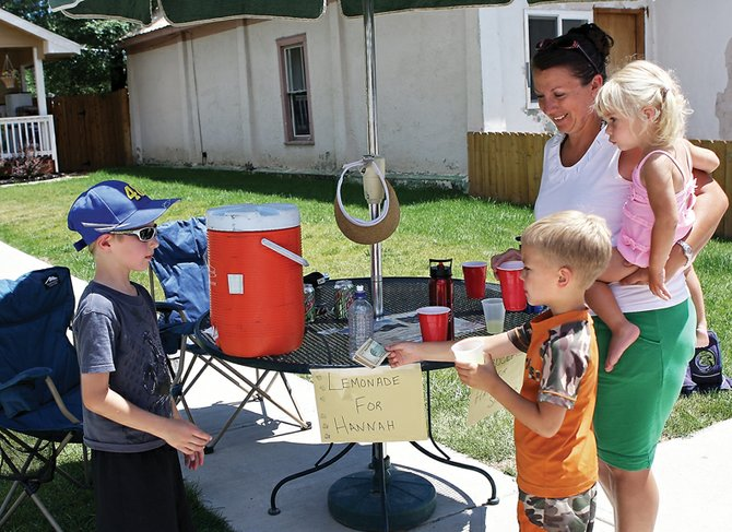 Tyler Burkett, 7, sells lemonade to Kody Feldmann, 5, his mother, Amy, and his sister, Kylie, 2, on Friday on Yampa Avenue. Tyler and his sister, Brianna, 9, operated the stand to raise money for former Craig resident Hannah Sixkiller, 7, who is being treated for brain cancer. The Feldmanns, who are Hannah's neighbors from Dixon, Wyo., came to Craig to use the community swimming pool, and noticed the stand while driving into town.