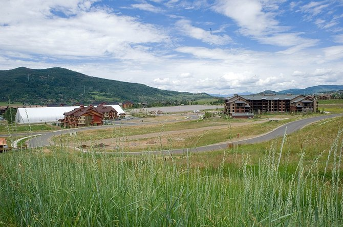 The development partnership behind Wildhorse Meadows intends to the city planning process in the fall with a new vision for its next phase, in spite of 40 unsold luxury condominiums in Trailhead Lodge, pictured at right.
