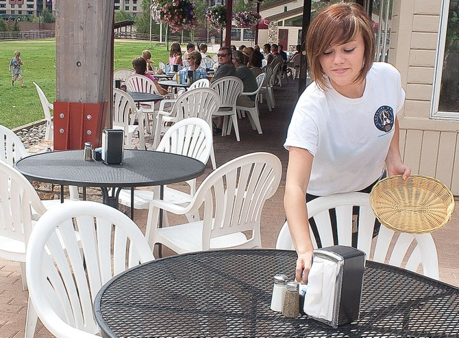 Waitress Lexi Flores sets up a table Monday afternoon at the Slopeside Grill in Torian Plum Plaza. Sales tax revenues from base area businesses increased more than 12 percent in June 2010 compared to June 2009.