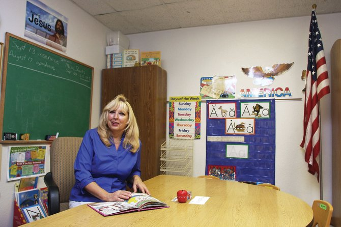 Linda Knoche, lead supervisor/kindergarten teacher, sits behind her desk Friday at Calvary Baptist School, located inside Calvary Baptist Church. The school is preparing for its first year of offering a Christian-based education to students in kindergarten through third grade.
