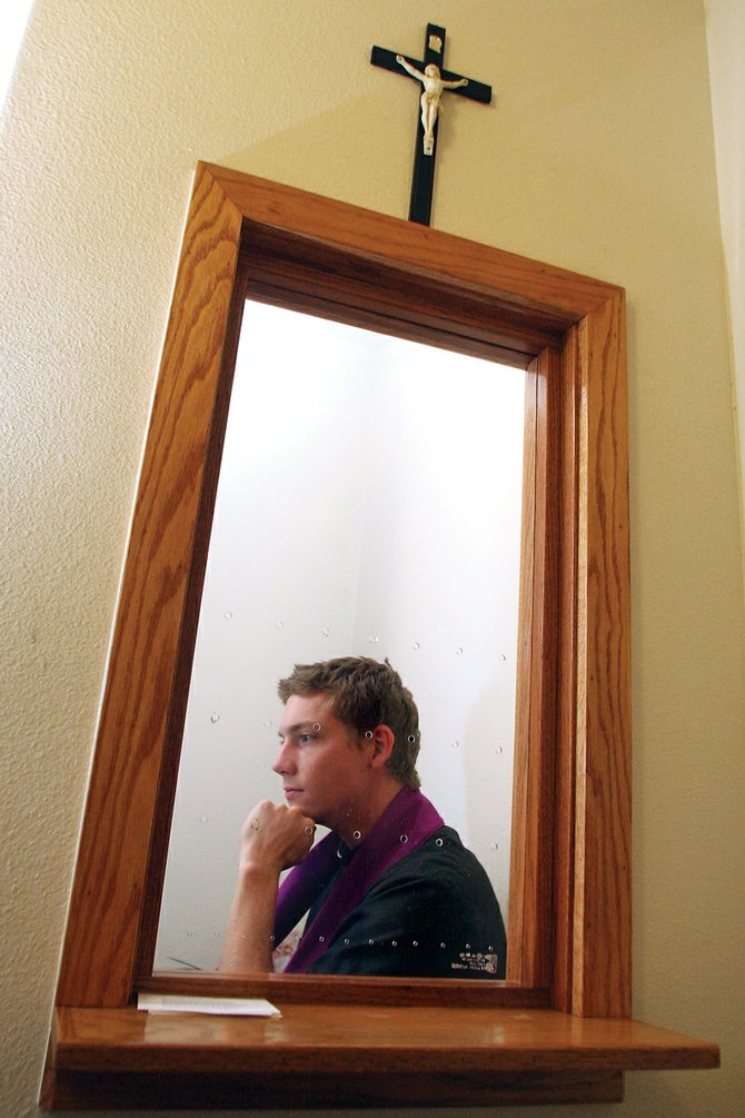 Father Michael Rapp sits in the confessional booth, with the separation curtain removed for the purpose of this photo, on Thursday at St. Michael Catholic Church in Craig. Rapp recently started his three-year assignment in Craig, and also serves congregations in Rangely and Meeker.