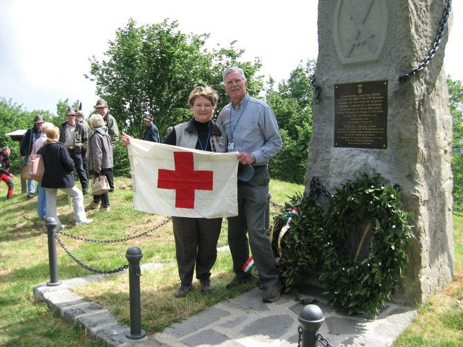 Nancy Kramer displays her father's army medic flag at the top of Mount Belvedere in Italy with her husband, Lynn. Kramer's father, Bill Robertson, served in the 10th Mountain Division during World War II. She is organizing a gathering of veterans and descendants of the division in Steamboat Springs.