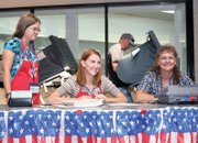 Moffat County election judges Kellie Looper, left, Brandi Meek, middle, and Cindel Nielson, wait to help voters like Robert Clayton, in back, use the electronic system Tuesday at the voting center at Centennial Mall. Area residents also had the opportunity to vote early or with mail-in ballots. Polls are open through 7 p.m. today.