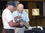 Ken Bergstron, left, drops his ballot in the box with the help of election judge Oscar King on Tuesday at the voting center at Centennial Mall. King has helped with local elections for more than 10 years and said he enjoys being part of the process.